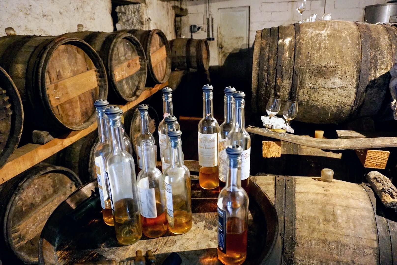 Many bottles of Sauternes wine sit on top of a wine barrel in a barrel cellar